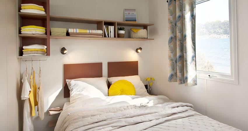 Slaapkamer met tweepersoonsbed van chalet 6 met terras